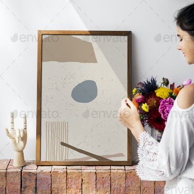 Girl decorating a wall with a frame mockup