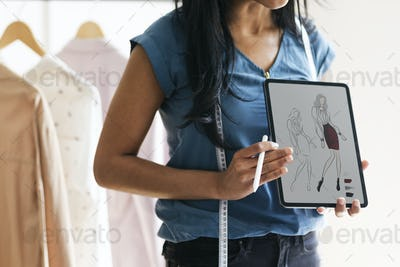 Fashion designer holding a tablet with a design drawing