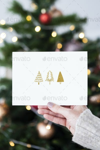 Woman holding a Christmas card in front of a Christmas tree mockup