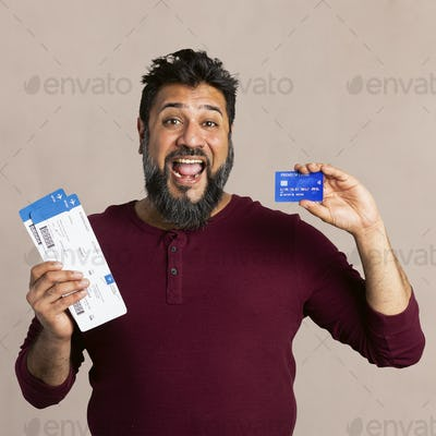 Excited Indian man holding a credit card and fligh tickets mockup
