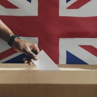 British man casting his vote to a ballot box