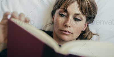 Woman reading a book on a bed during coronavirus quarantine