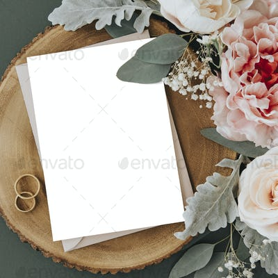 Invitation card, roses, and a ring on a table