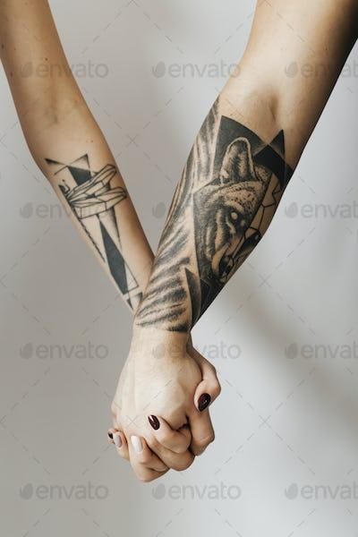 Tattooed hands holding hands psd