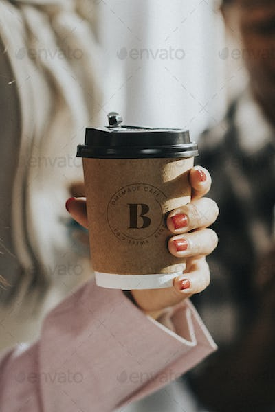 Female hand holding a coffee cup mockup