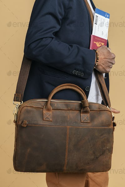 Man carrying a leather bag while boarding the plane