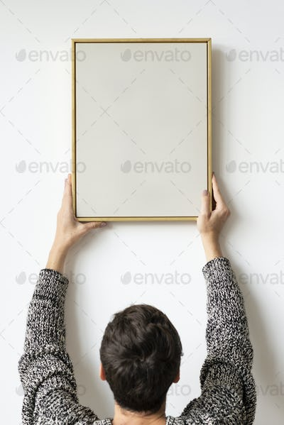 Woman in a black sweater hanging a wooden frame on a white wall mockup
