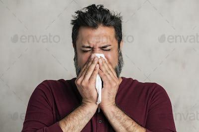 Sick Indian man blowing his nose