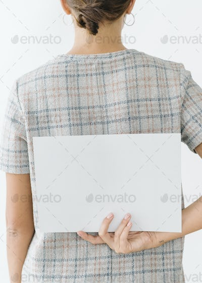 Woman in a gray plaid dress showing a blank card on her back