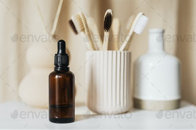 Brown dropper bottle and bamboo toothbrushes still life