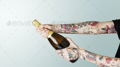 Tattooed hand holding a bottle of champagne