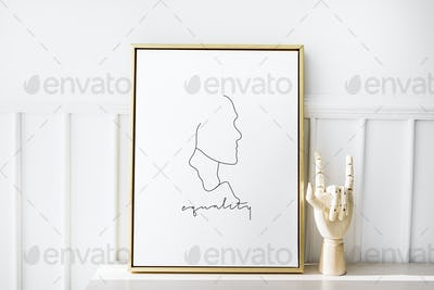 Gold photo frame by the hand mannequin on a white table