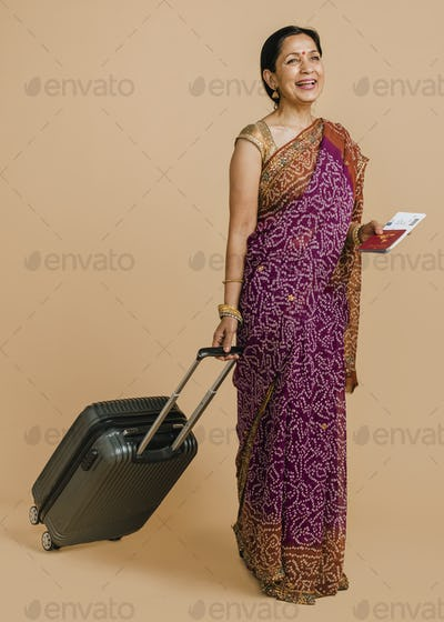 Happy Indian woman in a traditional saree ready for boarding