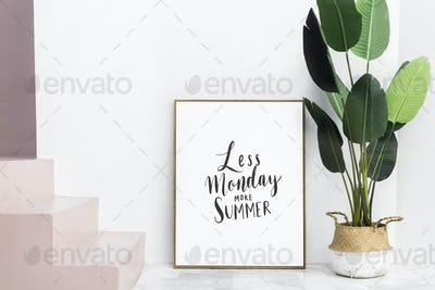 Gold photo frame by the houseplant on a floor