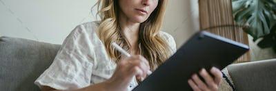 Woman using a stylus writing on a digital tablet  during coronav