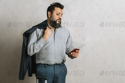Happy Indian businessman checking his flight ticket