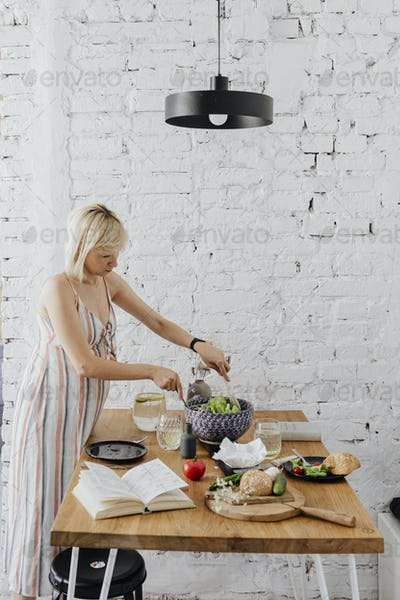 Pregnant woman cooking from a cookbook