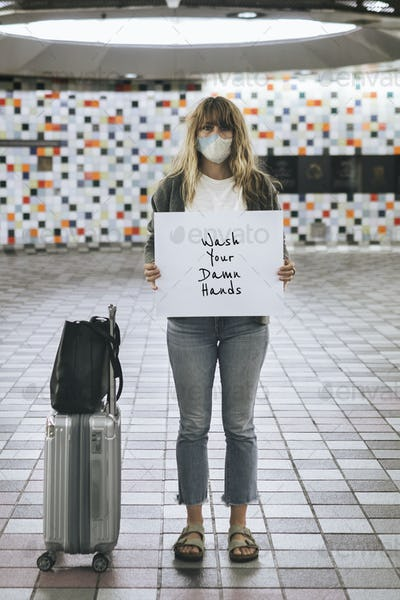 Woman with a suitcase holding wash your damn hands sign during the coronavirus outbreak