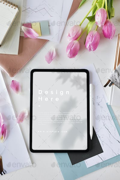 Digital tablet mockup on a table with flowers