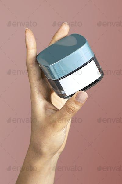 Hand holding face cream jar