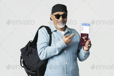 Happy black senior traveler with an air ticket and passport
