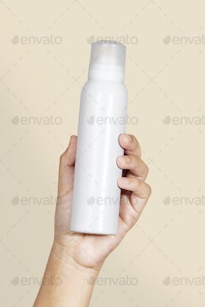 Black woman holding a white spray bottle