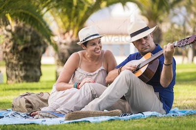 Romantic caucasian couple sitting on a meadow in spring - man play an acoustic guitar