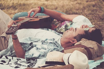 Romantic couple in love lay down singing a guitar and enjoying the outdoor leisure activity
