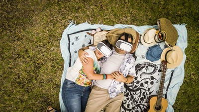 Alternative couple in relationship lay down i love with guitar and goggled headset