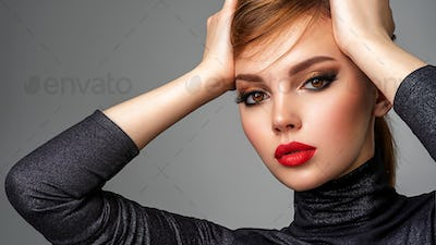Beautiful girl with red lips and short hair.  Closeup portrait of a model with bright makeup