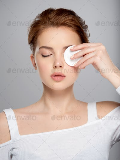 Beautiful face of a young Caucasian woman with a cotton pad in her hand, isolated