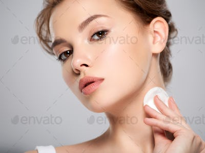 Beautiful face of a young Caucasian woman with a cotton pad in her hand, isolated.