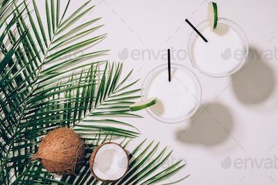 top view of organic coconuts, green palm leaves and coconut cocktails in glasses with drinking
