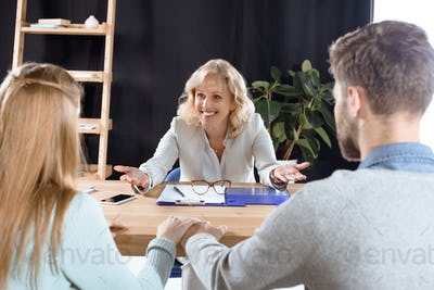 cheerful mature female psychologist talking with young couple