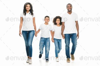 happy african american family holding hands while walking together isolated on white