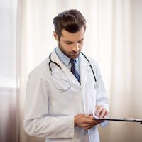 Pensive male doctor with stethoscope holding folder with medical documents