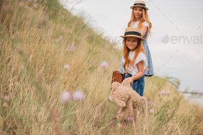 beautiful mother and daughter with suitcase and teddy bear holding hands while walking together on