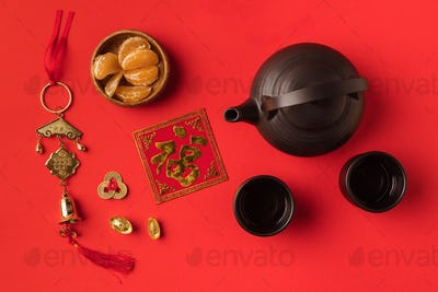 top view of oriental decorations, tangerines and tea set isolated on red