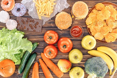 top view of fresh fruits with vegetables and assorted unhealthy food on wooden table