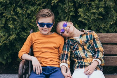smiling children in sunglasses holding hands while sitting on bench at park