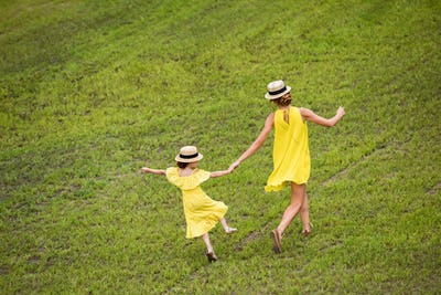 back view of pretty mother and daughter in yellow dresses holding hands while walking on green lawn