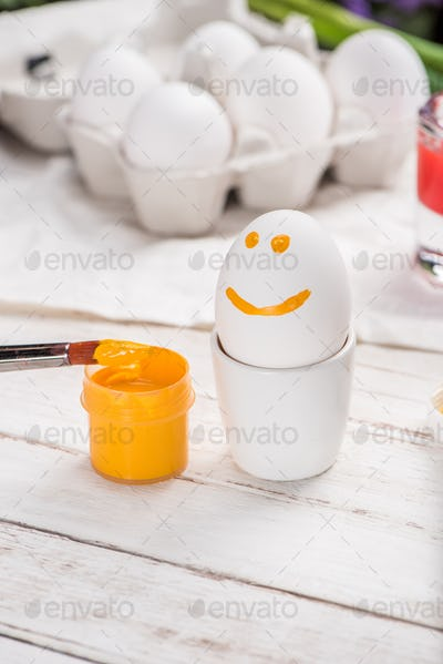 Close-up view of white egg with smiley face and open yellow paint container with brush