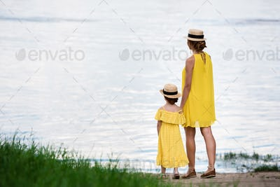 back view of pretty mother and daughter holding hands while standing at riverside