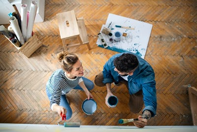 Top view of couple painting wall indoors at home, relocation and diy concept