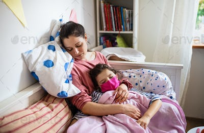 Tired mother looking after sick small daughter in bed at home, coronavirus concept