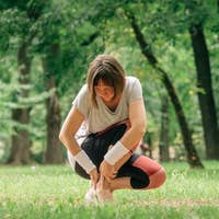 Female jogger with painful ankle injury during park jogging activity