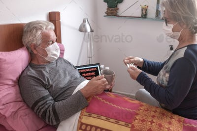 Sick elderly man of COVID-19 lies in bed at home wearing medical mask while wife takes care of him