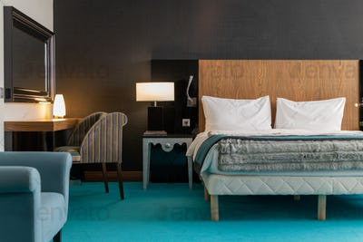 Interior of large luxurious hotel room with double bed, two armchairs, lamps, table and mirror