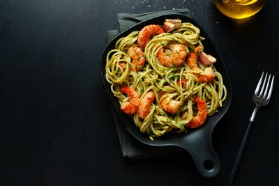 Pasta with shrimps and pesto on plate