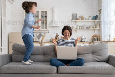 Tired mother sit on couch, work on laptop at home, hyperactive little kid jumping drawing attention.